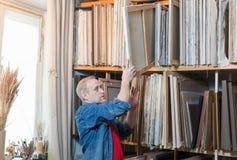 Męski artysta bierze obraz od szelfowego stojaka Fotografia Royalty Free