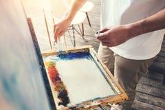 Męski artysta miesza kolory na palecie w studiu Malarz w warsztacie Zdjęcia Stock