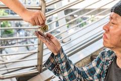 Męski bezdomny żebrak otrzymywa złocistą bitcoin monetę zdjęcia stock