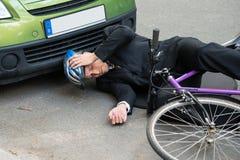 Męski cyklista po wypadku samochodowego na drodze Obraz Royalty Free