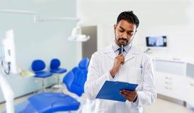 M?ski dentysta z schowkiem przy stomatologiczn? klinik? fotografia royalty free