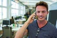 Męski dyrektor wykonawczy opowiada na telefonie komórkowym w biurze Zdjęcie Royalty Free