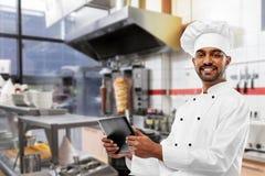 M?ski indyjski szef kuchni z pastylka komputerem osobistym przy kebabu sklepem zdjęcia stock