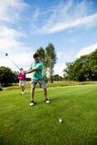 Męski instruktor pomaga kobiety w uczenie golfie Zdjęcia Stock