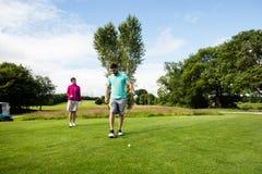 Męski instruktor pomaga kobiety w uczenie golfie Zdjęcie Royalty Free