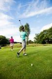 Męski instruktor pomaga kobiety w uczenie golfie Obrazy Stock