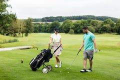 Męski instruktor pomaga kobiety w uczenie golfie Zdjęcia Royalty Free