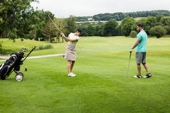 Męski instruktor pomaga kobiety w uczenie golfie Fotografia Stock