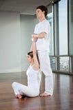 Męski joga instruktor Pomaga kobiety Fotografia Royalty Free