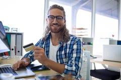 Męski kierownictwo robi online zakupy na laptopie przy jego biurkiem Obrazy Royalty Free