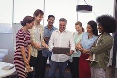 Męski kierownik pokazuje laptop koledzy w kreatywnie biurze Zdjęcia Stock