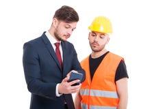 Męski konstruktor i biznesmen wyszukuje na telefonie komórkowym Fotografia Royalty Free