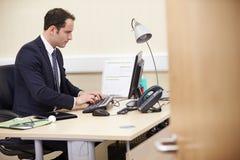 Męski konsultant Pracuje Przy biurkiem W biurze Obraz Stock