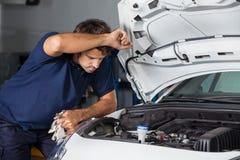 Męski mechanik Egzamininuje Samochodowego silnika Zdjęcia Royalty Free