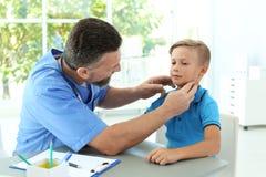 Męski medyczny asystent egzamininuje dziecka zdjęcia royalty free