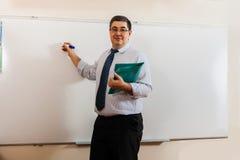 Męski nauczyciel pisze na blackboard Zdjęcie Royalty Free