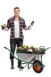 Męski ogrodniczki mienia kwiat w garnku i rydlu Zdjęcia Stock