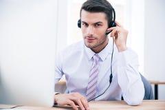 Męski operatora obsiadanie przy jego miejscem pracy w biurze Zdjęcia Stock
