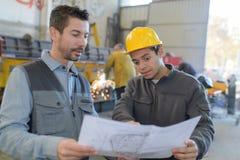 Męski pracownik fabryczny i nadzorca analizuje plany Obraz Royalty Free