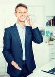 Męski pracownika odpowiadanie na telefonie przy biurem Obrazy Stock