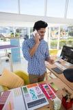 Męski projektant grafik komputerowych opowiada na telefonie komórkowym przy biurkiem Obrazy Royalty Free