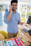 Męski projektant grafik komputerowych opowiada na telefonie komórkowym przy biurkiem Zdjęcie Stock