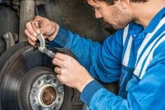 Męski Samochodowy mechanik Egzamininuje Hamulcowego dyska Z Caliper Zdjęcia Royalty Free