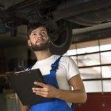 Męski samochodowy mechanik pracuje pod samochodem Obrazy Royalty Free