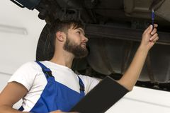 Męski samochodowy mechanik pracuje pod samochodem Zdjęcia Royalty Free