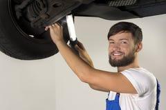 Męski samochodowy mechanik pracuje pod samochodem Obrazy Stock