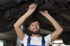Męski samochodowy mechanik pracuje pod samochodem Zdjęcia Stock