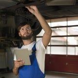 Męski samochodowy mechanik pracuje pod samochodem z pastylka pecetem Zdjęcie Stock