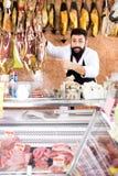 Męski sklepowy asystent demonstruje jamon Zdjęcia Stock