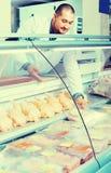 Męski sklepowy asystent sprzedaje koszernego kurczaka przy kontuarem i smilin Obraz Royalty Free