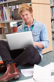 Męski studenta collegu studiowanie W bibliotece Z laptopem Obrazy Stock