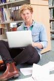 Męski studenta collegu studiowanie W bibliotece Z laptopem Zdjęcie Royalty Free