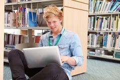 Męski studenta collegu studiowanie W bibliotece Z laptopem Obraz Royalty Free