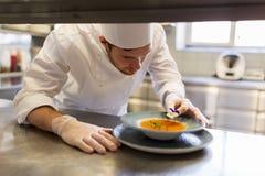 Męski szef kuchni dekoruje naczynie z pansy kwiatem Obrazy Stock