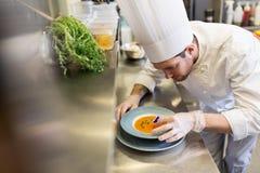 Męski szef kuchni dekoruje naczynie z pansy kwiatem Zdjęcie Royalty Free