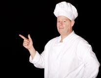 Męski szef kuchni wskazuje na czarnym tle Zdjęcia Stock