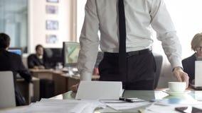 M?ski szef patrzeje przez dokumentaci i pije herbaty, stoi w jego biurze fotografia stock