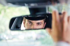 Męski szofer patrzeje jego odbicie w lustrze Fotografia Royalty Free