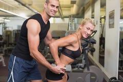 Męski trener pomaga kobiety z dumbbell w gym Zdjęcia Royalty Free