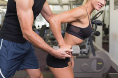 Męski trener pomaga kobiety z dumbbell w gym Fotografia Stock