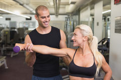 Męski trener pomaga kobiety z dumbbell w gym Obraz Stock