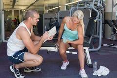Męski trener pomaga kobiety z dumbbell w gym Zdjęcia Stock