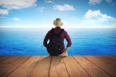Męski turysta siedzi na drewnianym doku Obraz Stock