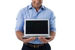 Męski wykonawczy mienie laptop Fotografia Royalty Free