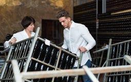 Męskie pracownika odtransportowania wina butelki magazyn Fotografia Stock