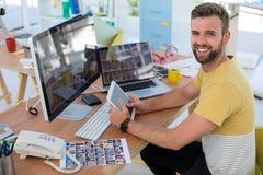 Męskie wykonawcze patrzeje fotografie przy biurkiem Fotografia Royalty Free